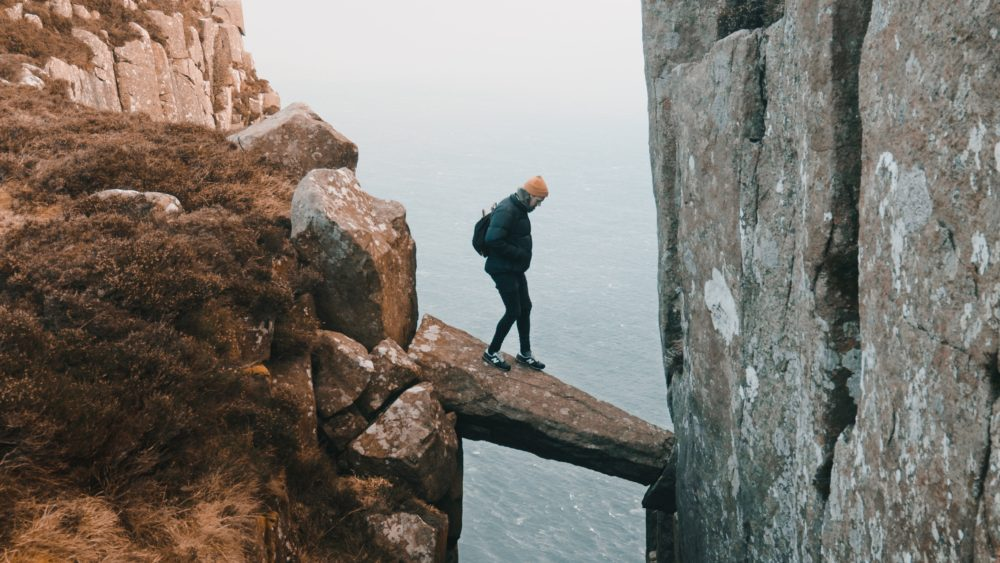 man hiking standing on a rock